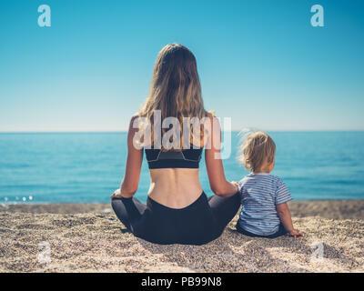 Una giovane madre in usura fitness è rilassante sulla spiaggia con il suo bambino Foto Stock