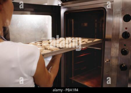 Il panettiere femminile mettendo una teglia piena di rotoli in forno. Donna rotoli di cottura in un forno. Foto Stock
