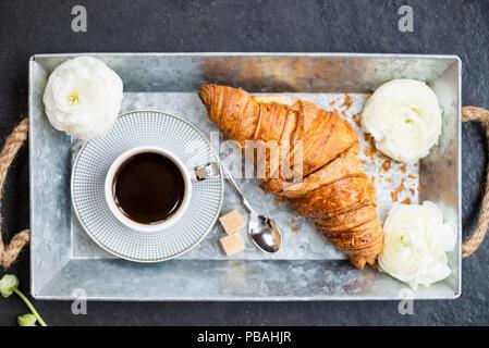 Colazione Leggera da croissant fresco e la tazza di caffè sul vassoio grigio, ranuncoli fiori nelle vicinanze Foto Stock