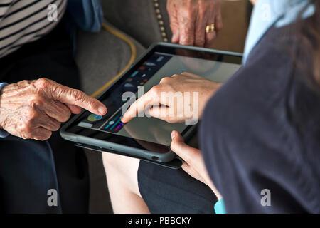 Giovani schoolgirl insegnare abilità informatiche per senior citizen su tablet sulla spalla pov Foto Stock
