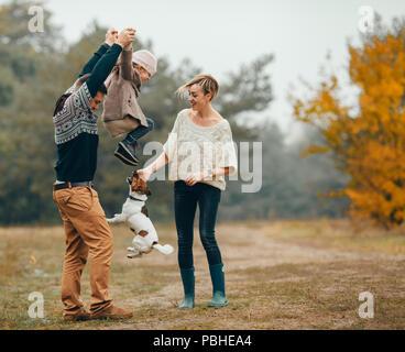 Genitori felici avere divertimento e sollevare la loro figlia al percorso di foresta accanto al salto cane durante la passeggiata nella foresta di autunno. Foto Stock