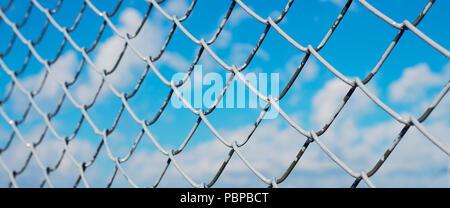 Un recinto fatto di maglia di filo metallico, netting coperti di bianco su uno sfondo di cielo azzurro e sole Foto Stock