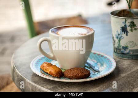 Classico cappuccino schiumoso Tazza da caffè con cracker e versare su un marmo ristorante tabella Foto Stock