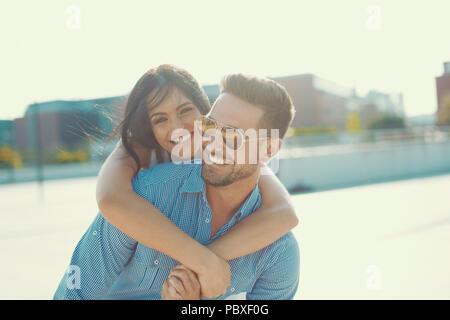 Felice giovane donna abbracciando elegante da uomo torna all'aperto nel tramonto, piggyback ride Foto Stock