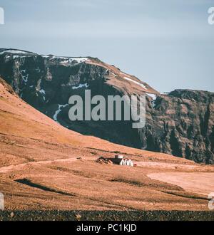 Tipico paesaggio islandese con case bianco rosso tetto contro le montagne del piccolo villaggio nel sud dell'Islanda. Foto Stock