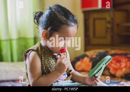 Felice Asian baby boy divertendosi con mangiare lecca-lecca.Bambini aventi lecca-lecca Foto Stock
