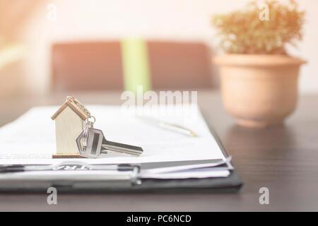 Chiave di casa sulla carta contratto di preparazione per il proprietario sulla tavola in banca Foto Stock