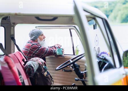 Senior uomo vicino al suo ritiro, pronto per una passeggiata nei boschi Foto Stock