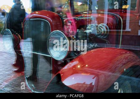 Vintage auto rossa con grandi fari tondi e la riflessione nella finestra di sagome di passanti sul marciapiede della strada Foto Stock