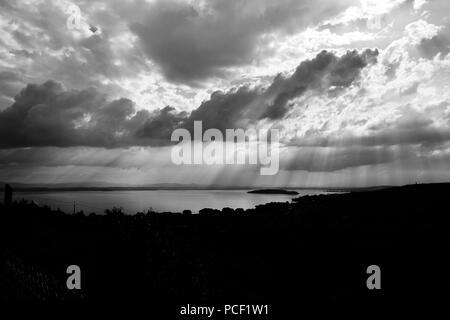 Raggi di sole che fuoriesce attraverso le nuvole sopra un isola in un lago Foto Stock