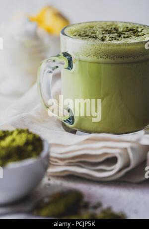 BULLETPROOF MATCHA. Ketogenic dieta cheto bevanda calda. Il tè matcha miscelato con olio di noce di cocco e il burro. Tazza di bulletproof matcha e ingredienti su sfondo bianco Foto Stock