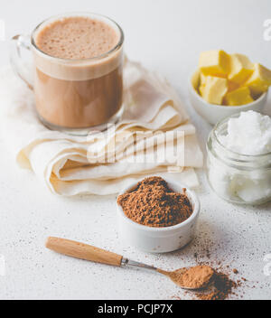 BULLETPROOF CACAO. Ketogenic dieta cheto bevanda calda. Cacao miscelata con olio di noce di cocco e il burro. Tazza di cacao antiproiettile e gli ingredienti su sfondo bianco Foto Stock