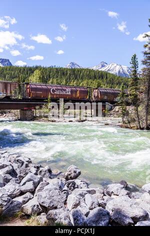 Un treno merci della Canadian Pacific Railway attraversando il Fiume Bow nelle montagne rocciose presso la città di Lake Louise, Alberta, Canada Foto Stock