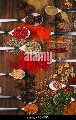Vista superiore del tavolo di legno pieno di spezie in cucchiai, puoi vedere i più popolari condimenti e stagionatori Foto Stock