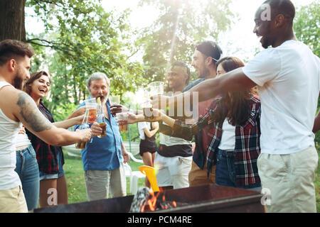 Gruppo di amici fare barbecue nel cortile. concetto circa il bene e stato d'animo positivo con gli amici Foto Stock