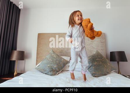Gioiosa bambina di saltare sul letto con Teddy bear. Bambino ragazza che gioca sul letto nella sua camera da letto e sorridente. Foto Stock