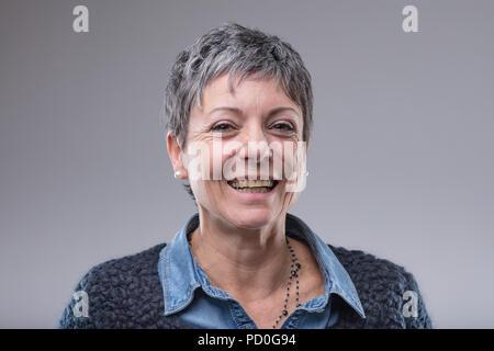 ... Sorridendo felice vecchio donna con capelli corti dando la telecamera  un raggiante sorriso amichevole isolato su 04b91d7349b4