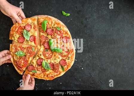 La gente mani prendendo fette di pizza italiana. Pizza italiana e le mani vicino fino su sfondo nero, vista dall'alto, copia dello spazio. Foto Stock
