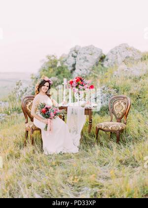 La bella sposa con il bouwuet è seduto sulla sedia antica vicino alla tabella di nozze in montagna. Foto Stock