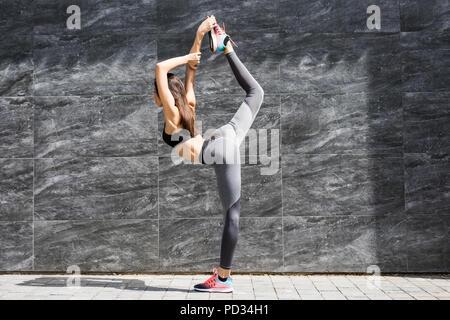 Giovane donna fitness facendo warm-up di esercizio prima di eseguire lo stiramento la gamba eseguendo il ginocchio al petto tratto sulla strada della citta'. Atleta sportivo pr Foto Stock