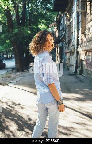 Giovane donna con capelli naturalmente ricci in piedi in città sulla strada verde al giorno d'estate e di sole. Verticale immagine candidi di moda donna girando intorno a Foto Stock