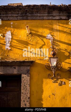 Lanterna a muro sulla facciata fatiscente, San Miguel De Allende, un'era coloniale città, regione di Bajío, Messico Centrale Foto Stock