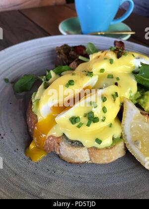 Uovo in camicia su pane, pancetta e limone su una lastra grigia Foto Stock