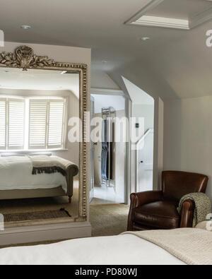 Poltrona in pelle e di un grande specchio nella camera da for Poltrona letto pelle
