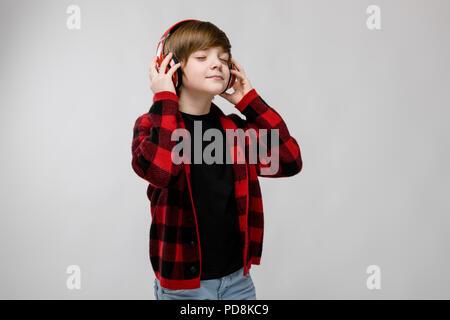Ragazzo adolescente nel quartiere alla moda di clother e cuffie Foto Stock 766a018e3608