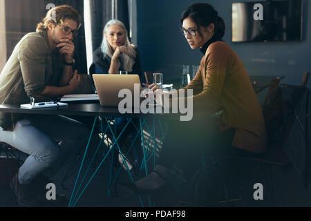 Tre persone sedute intorno ad un tavolo e guardando il laptop. Business donna mostra analisi di progetto su laptop ai colleghi. Foto Stock
