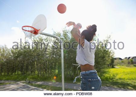 Giovane donna che gioca a basket Park Campo da pallacanestro Foto Stock