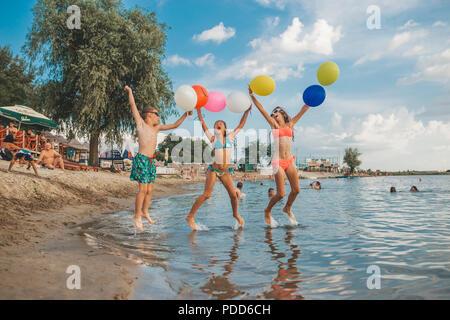 Dei bambini felici giocando con palloncini in mare. Bambini il divertimento all'aperto. La vacanza estiva e uno stile di vita sano concetto Foto Stock