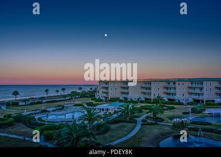 Una luna piena in un chiaro Cielo di tramonto sulla spiaggia condos Foto Stock
