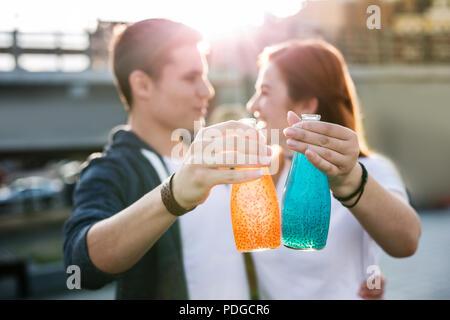Bottiglie di bevande in mani di gioiosa giovani Foto Stock