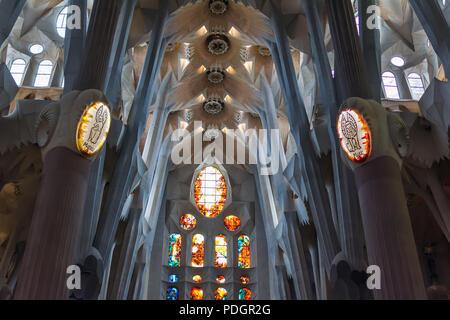 Dettagli architettonici di coloratissimi vetrata, soffitto e luci su colonne all'interno della Sagrada Familia - grande incompiuta Chiesa Cattolica Romana Foto Stock