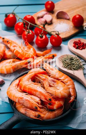 Alta Vista angolo di blu tavolo in legno pieno di gamberi e alcuni ingredienti per condire le verdure e mescolarle, concetto di ricette e ristoranti Foto Stock