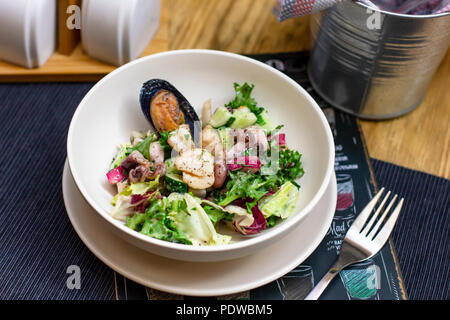 Insalatina tiepida di frutti di mare cozze, polpo e verdure fresche in piastra di profondo sul tavolo Foto Stock