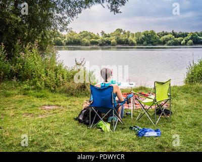 Ragazza giovane o donna siede a un tavolo da picnic che si affaccia sul lago a Neigh Bridge Country Park, nel Gloucestershire. Foto Stock