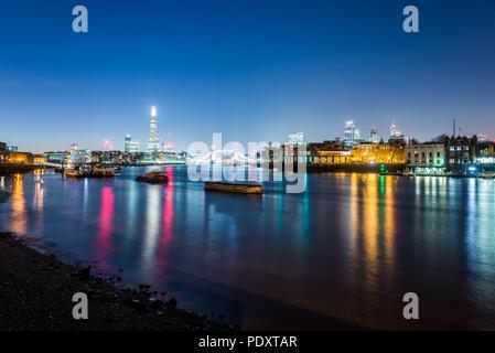 La skyline di Londra di notte come si vede dalle sponde del fiume Tamigi in Rotherhithe Foto Stock