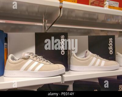 White Adidas sneakers visualizzata su ripiani di deposito di pattino. Foto  Stock 7439ec91ad3