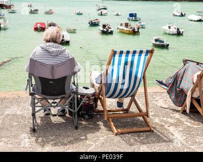 ST IVES, Inghilterra - 19 giugno: OAP matura in seduta sdraio per godersi il sole in St Ives Harbour. In St Ives, Inghilterra. Il 19 giugno 2018. Foto Stock