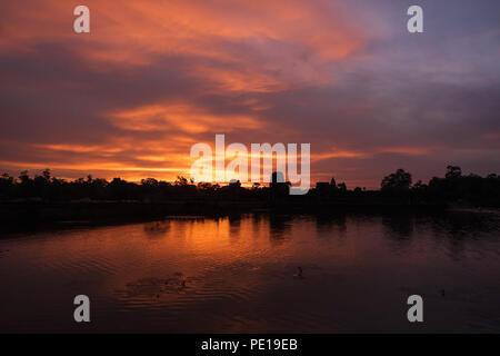 Sunrise oltre il fossato che circonda il tempio di Angkor Wat - il più grande monumento religioso nel mondo - vicino a Siem Reap, Cambogia Foto Stock