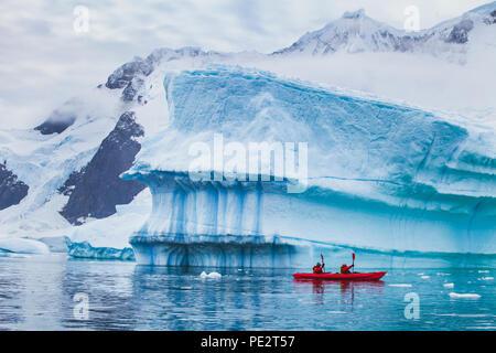 Inverno in kayak in Antartide, extreme sport avventura, persone pagaiando sul kayak nei pressi di iceberg Foto Stock