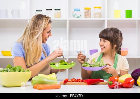 Felice madre e figlia godere di fare e avente un sano pasto insieme al loro domicilio. Foto Stock