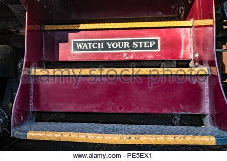 Vintage red train passi con guarda il tuo passo segno. Foto Stock