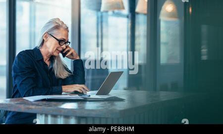 Senior business donna parlando al cellulare mentre si lavora sul computer portatile in ufficio. Femmina matura utilizzando laptop e parlando al telefono cellulare.