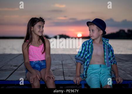 Ragazzo e una ragazza giocando sulla spiaggia al tramonto del tempo. Primo amore.Contenti i bambini godendo il lago pur avendo un buon tempo. Foto Stock