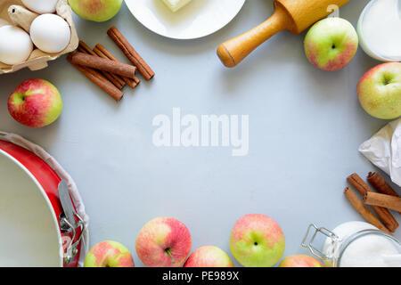 Gli ingredienti per cucinare la torta di mele. Raccolto fresche Mele, cannella, farina, zucchero, burro, uova, latte e stampo da forno in grigio sullo sfondo di legno. Foto Stock