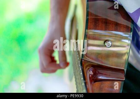 Giovane uomo seduto in autunno park con la chitarra Foto Stock