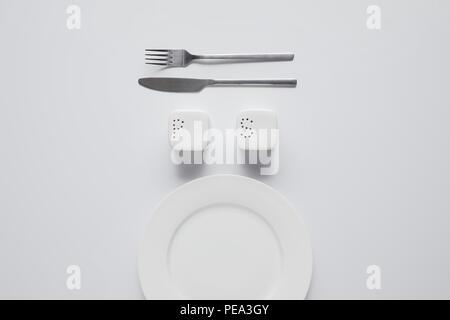 Vista superiore della piastra disposta, forcella, coltello, saltcellar e pepe caster sul tavolo bianco, concetto minimalista
